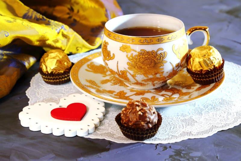 Día del ` s de la tarjeta del día de San Valentín, un símbolo del amor Todavía vida - té en un de oro fotos de archivo