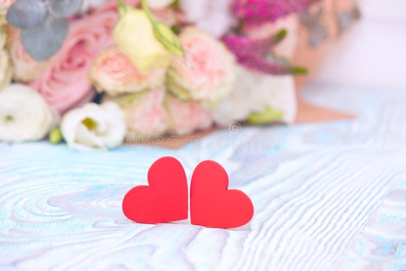 Día del `s de la tarjeta del día de San Valentín Valentine Gift Corazones y ramo rojos de flores en fondo de madera azul Diseño h fotos de archivo libres de regalías