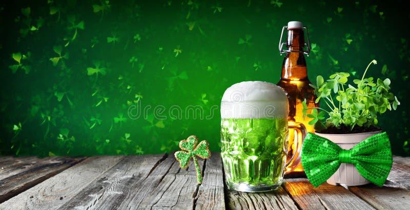 Día del ` s de St Patrick - cerveza verde en vidrio con la botella y los tréboles foto de archivo