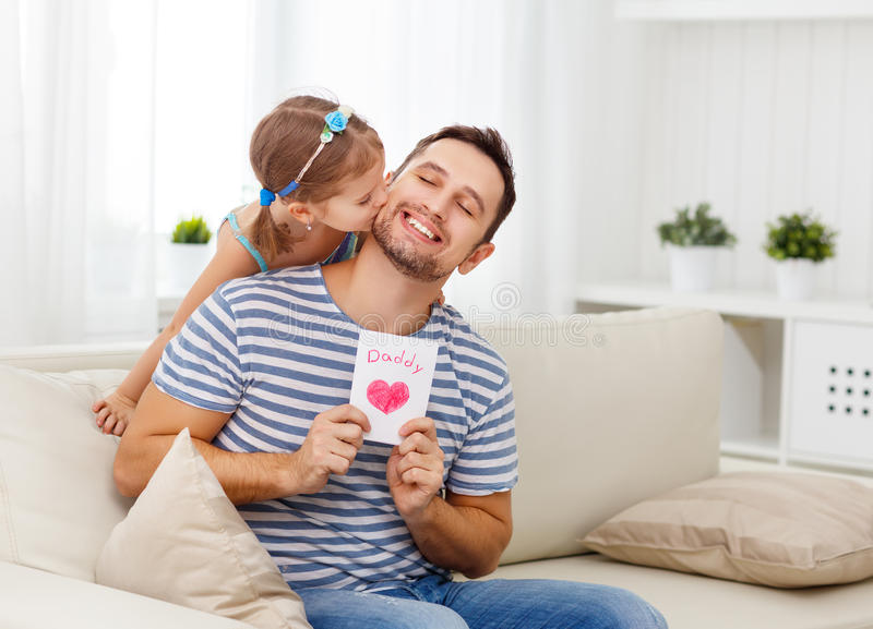 Día del `s del padre Hija feliz de la familia que da la tarjeta de felicitación del papá foto de archivo