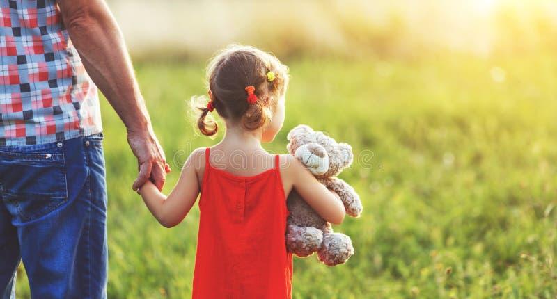 Día del `s del padre Muchacha del niño que abraza al padre en naturaleza en la puesta del sol foto de archivo libre de regalías
