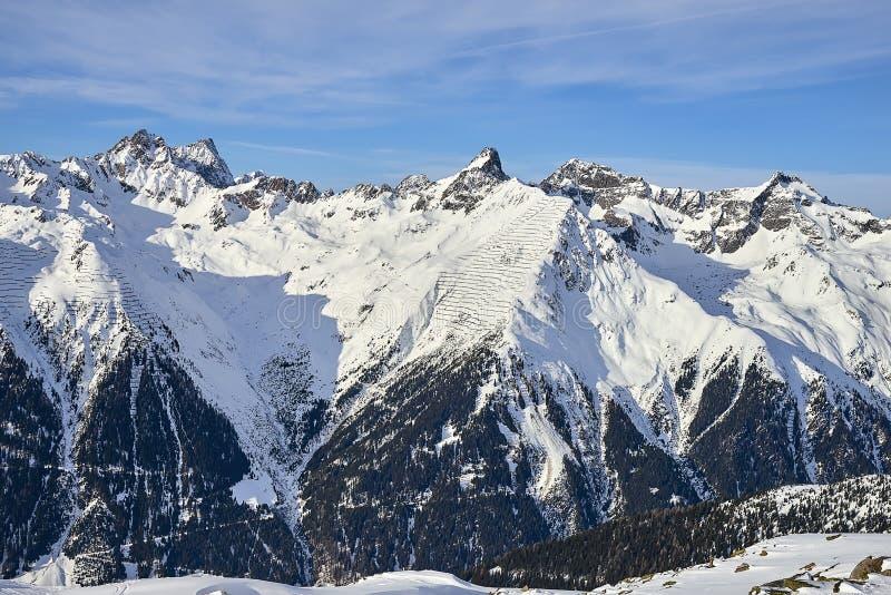 Día en las montañas de Silvretta - opinión de Sunny December del invierno sobre las cuestas de montaña nevadas y el cielo azul Au foto de archivo libre de regalías
