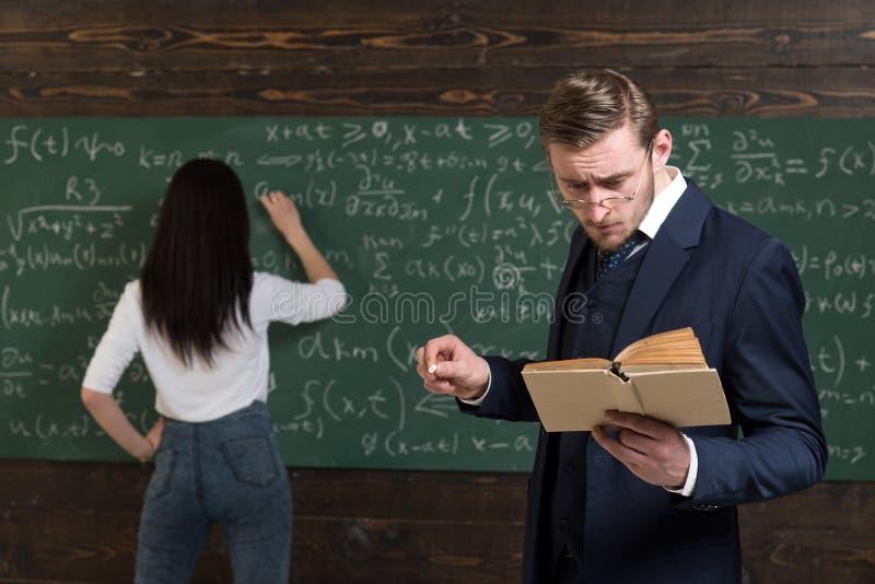 Día escolar El hombre del profesor en vidrios leyó la declaración de problema del libro de texto a la estudiante El aprendizaje d fotos de archivo