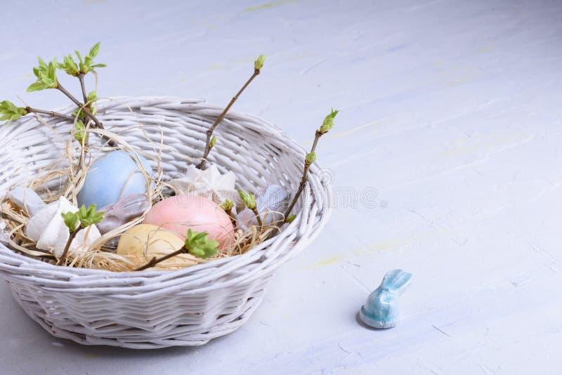 Día feliz de pascua, el pollo coloreado eggs, decoración en colores pastel en una cesta con la primavera ramifica Ciérrese para a foto de archivo libre de regalías