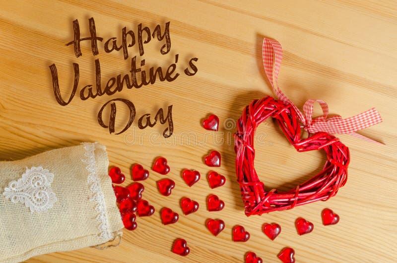Día feliz del ` s de la tarjeta del día de San Valentín de la muestra del corazón en una textura de madera, y el derramarse fuera imagenes de archivo