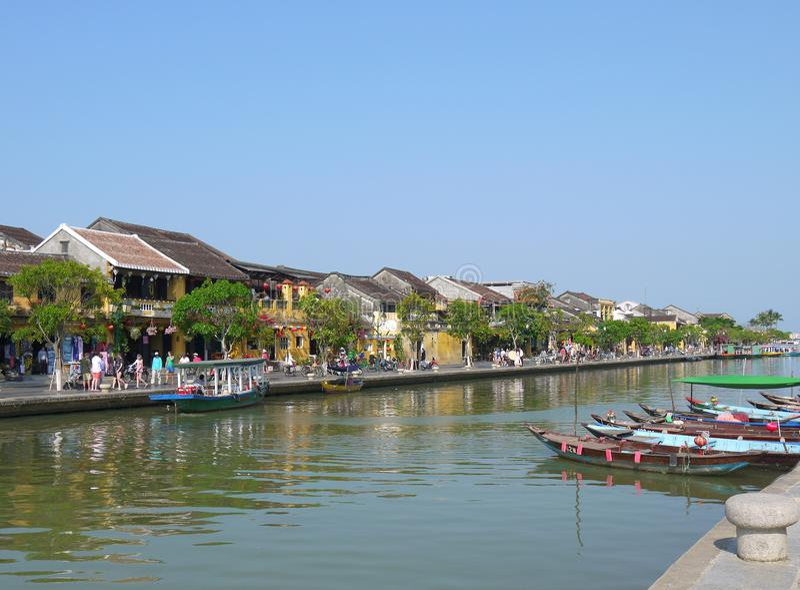 Día hermoso en la ciudad antigua de Hoi An con la opinión barcos tradicionales, casas amarillas y turistas fotografía de archivo