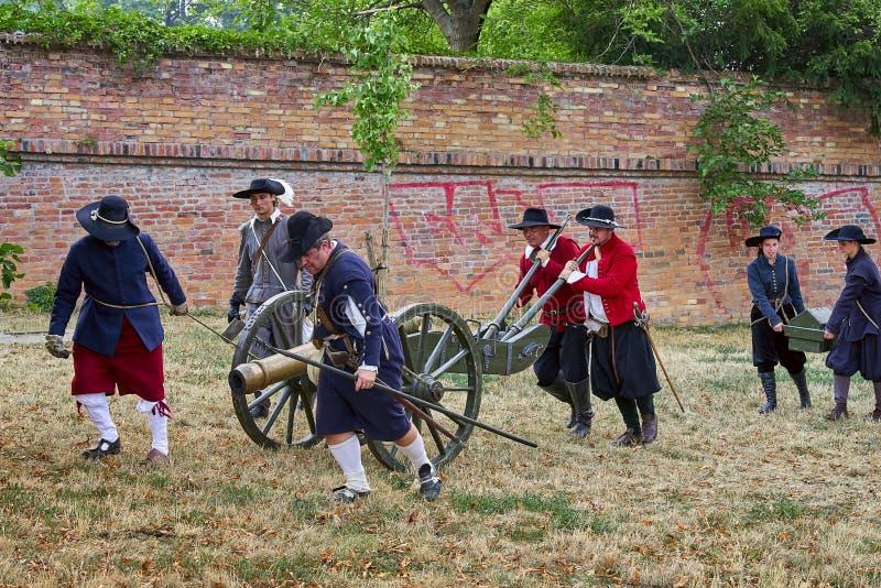 Día histórico de la reconstrucción de Brno Los actores en trajes históricos de la infantería preparan el cañón para atacar la pue imagenes de archivo