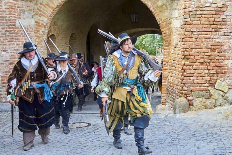 Día histórico de la reconstrucción de Brno Los soldados de infantería en trajes históricos salen a través de las puertas del cast imagenes de archivo