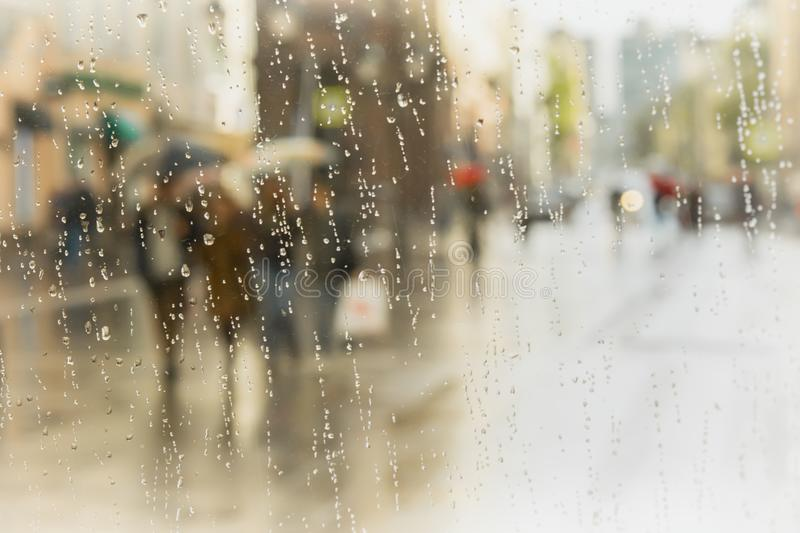 Día lluvioso en ciudad Silueta de la gente con el paraguas visto a través de las gotas de agua sobre el vidrio de la ventana Foco imagen de archivo