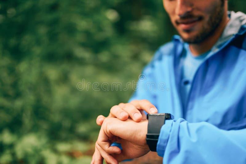 Día masculino apto del basculador usando un smartwatch durante la raza del rastro del bosque del campo a través en un parque de n foto de archivo