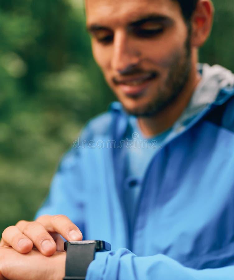 Día masculino apto del basculador usando un smartwatch durante la raza del rastro del bosque del campo a través en un parque de n fotos de archivo