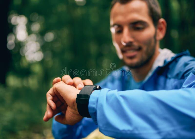 Día masculino apto del basculador usando un smartwatch durante la raza del rastro del bosque del campo a través en un parque de n imagen de archivo