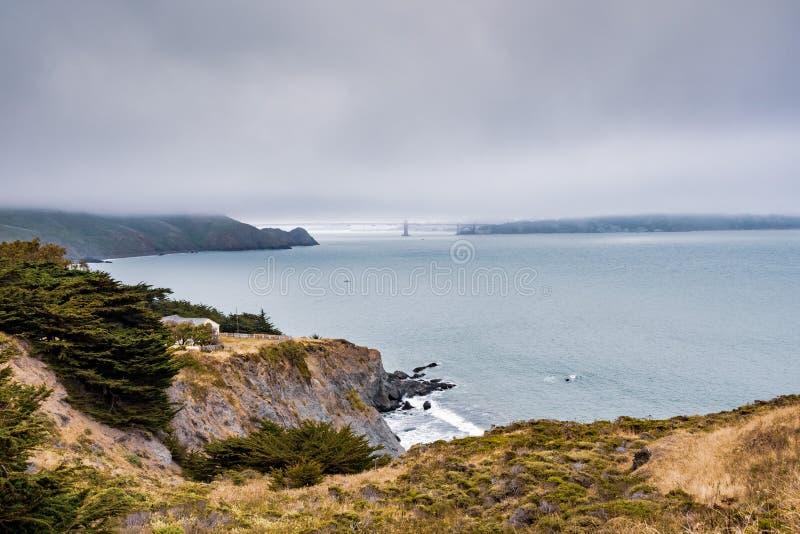 Día nublado en la costa costa del Océano Pacífico; Puente Golden Gate cubierto por la niebla visible en el fondo; Marin Headlands fotos de archivo