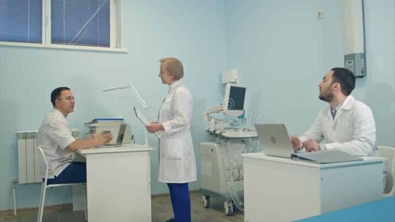 Día ocupado en el hospital para el personal médico que trabaja en oficina imágenes de archivo libres de regalías