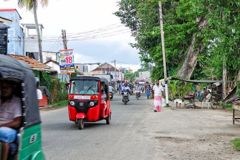 día ordinario en la calle en pequeño pueblo asiático, la gente se mueve en su negocio en una motocicleta, tuk del tuk imagenes de archivo