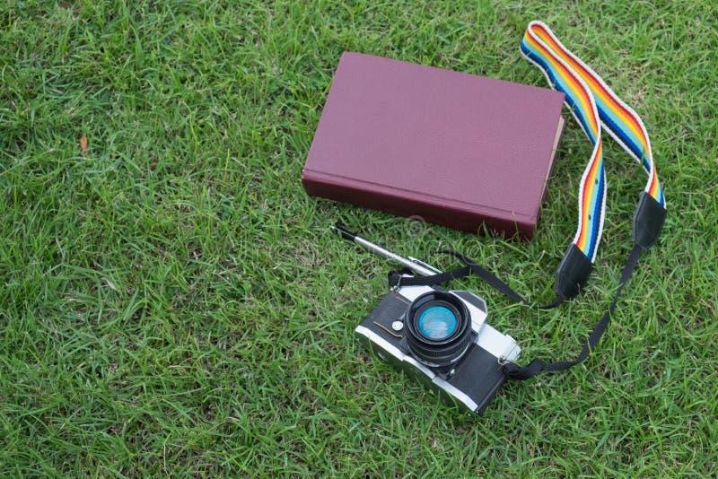 Día soleado apagado con la pluma y la cámara del libro foto de archivo