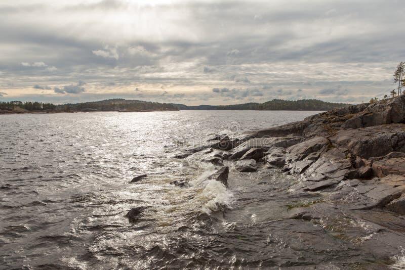 Día soleado en la orilla rocosa del lago fotografía de archivo