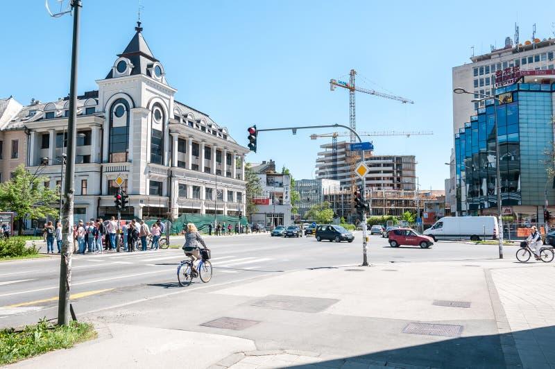 Día soleado hermoso con la gente, los coches y el nuevo sitio de la construcción de edificios con las grúas en la distancia Abril fotos de archivo