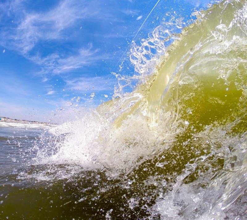 Día soleado que se estrella de la onda en la playa imagen de archivo
