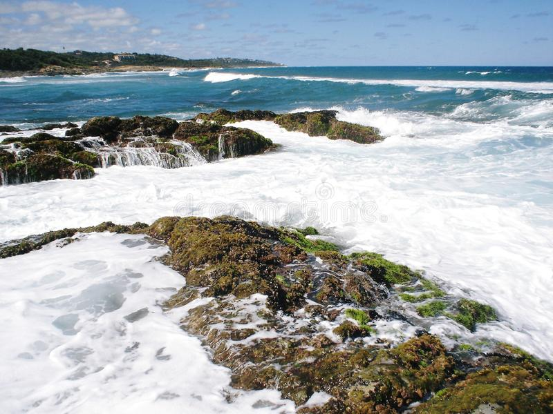 Día surafricano fresco de la playa con las ondas que se estrellan sobre rocas imagenes de archivo