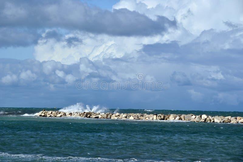 Día ventoso en el mar con las ondas grandes contra rocas foto de archivo libre de regalías
