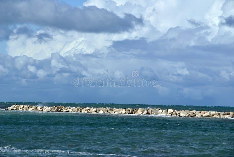 Día ventoso en el mar con las ondas grandes contra rocas foto de archivo
