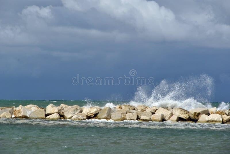 Día ventoso en el mar con las ondas grandes contra rocas fotos de archivo