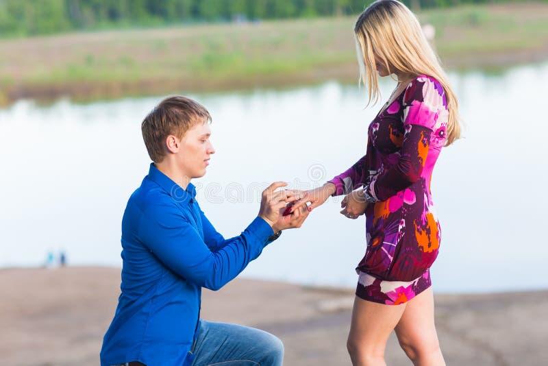 Días de fiesta, amor, pares, relación y concepto de la datación - hombre romántico que propone a una mujer en la naturaleza foto de archivo libre de regalías