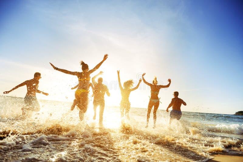 Días de fiesta de la playa de la puesta del sol de los amigos de la gente de la muchedumbre imagen de archivo