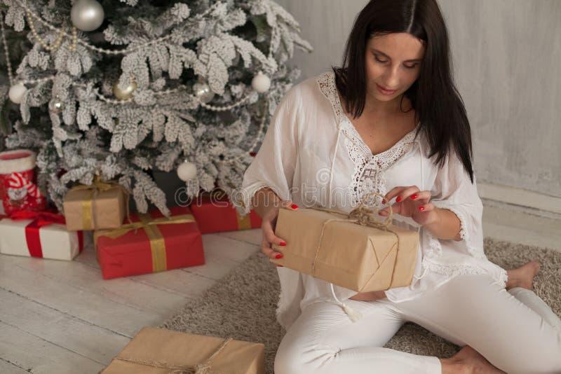Días de fiesta de los regalos del Año Nuevo del árbol de navidad de la mujer embarazada foto de archivo libre de regalías
