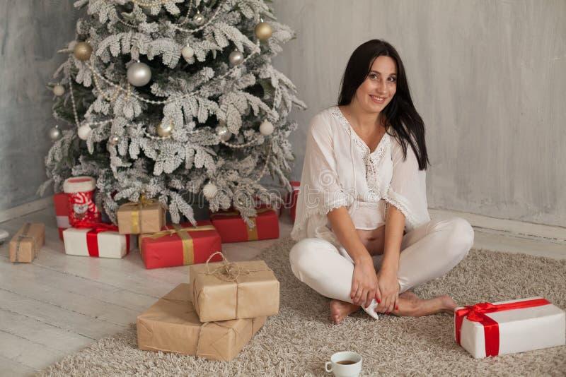 Días de fiesta de los regalos del Año Nuevo del árbol de navidad de la mujer embarazada imagen de archivo libre de regalías