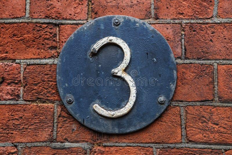 Dígito 3 en fondo oscuro del metal en la pared de ladrillo roja imagen de archivo libre de regalías