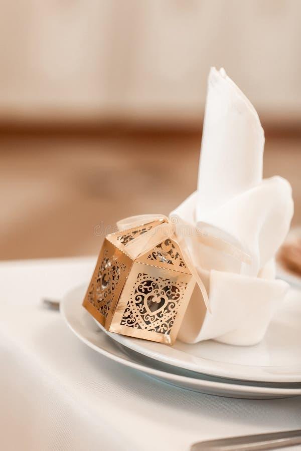 Dîner à table festif, boîte cadeau Gold et couverts sur des plats blancs Service, définition de la table photographie stock