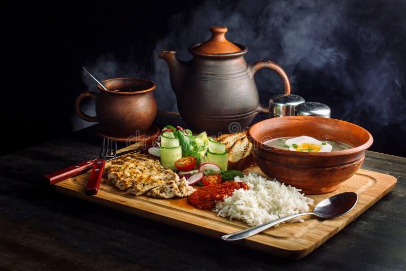 Dîner étendu sur la soupe à table, à oignon et à oeufs, riz, blanc de poulet photos stock