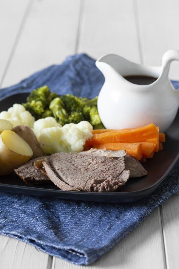 Dîner de déjeuner de dimanche de rôti d'agneau avec des légumes d'un plat de noir d'aquare, avec la cruche de sauce au jus, sur u image libre de droits