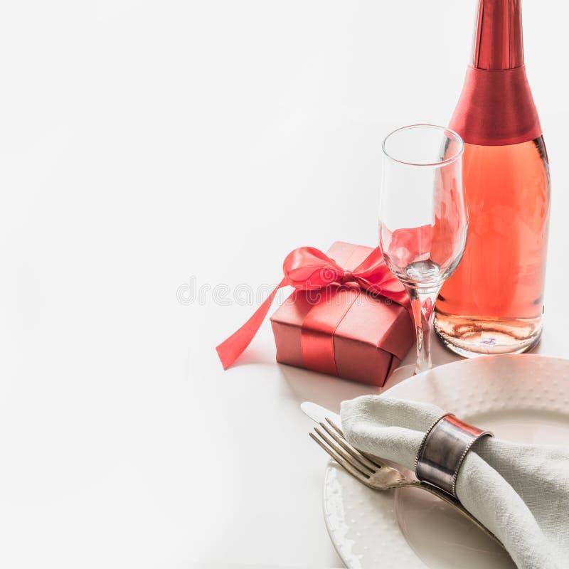 Dîner de jour de valentines avec le couvert de table avec le cadeau rouge, une bouteille de champagne sur le blanc Fin vers le ha photo libre de droits