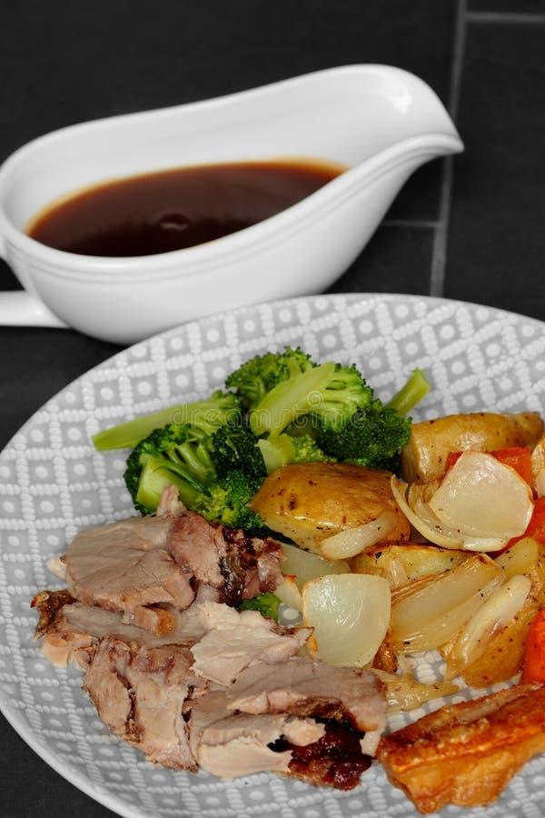 Dîner de rôti de porc avec les légumes et la sauce au jus images stock