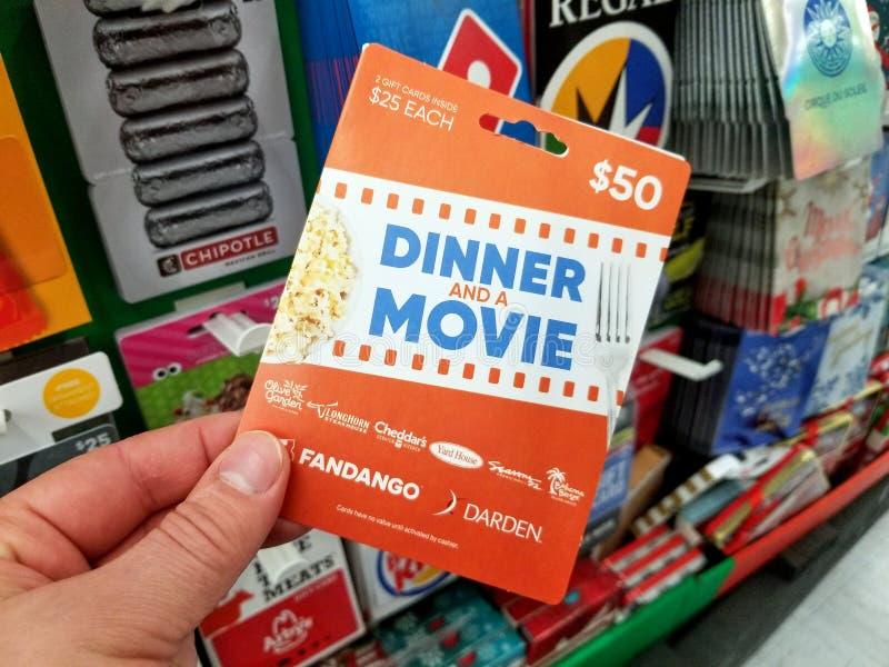 Dîner et un chèque-cadeau de film dans une main images libres de droits