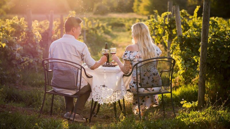 Dîner romantique avec l'échantillon de vin dans un endroit au coucher du soleil images libres de droits