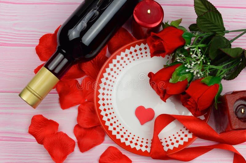 Dîner romantique avec les roses rouges et les pétales sur la table image stock