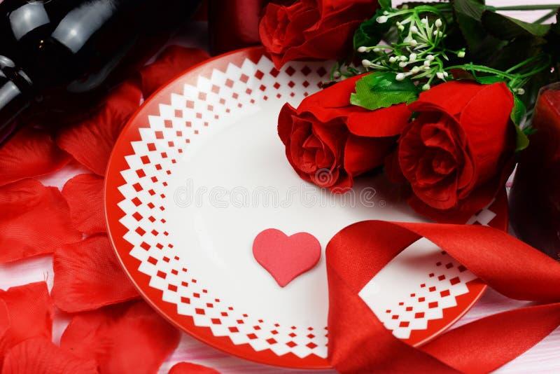 Dîner romantique avec les roses rouges et les pétales sur la table images stock