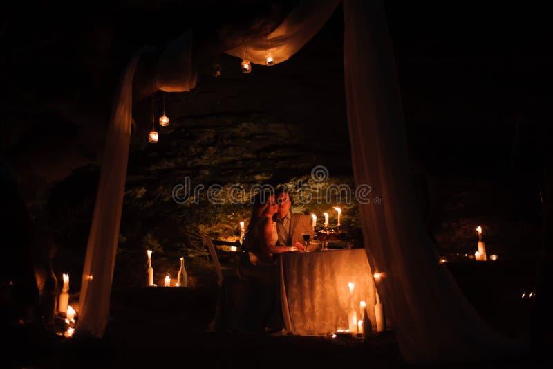 Dîner romantique d'un jeune couple par lueur d'une bougie dans les montagnes photo stock