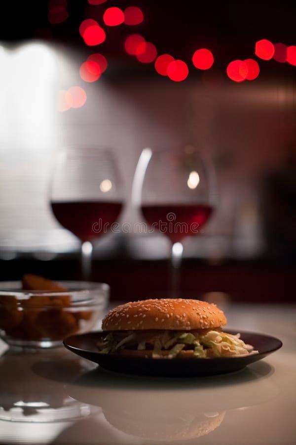 Dîner romantique : Deux verres de vin et d'hamburger de jucy, pépites sont à l'arrière-plan foncé avec des lumières de nouvelle a photographie stock