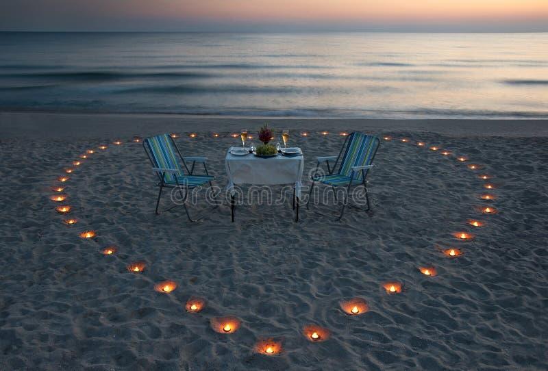Dîner romantique sur la plage de mer avec le coeur de bougie image libre de droits