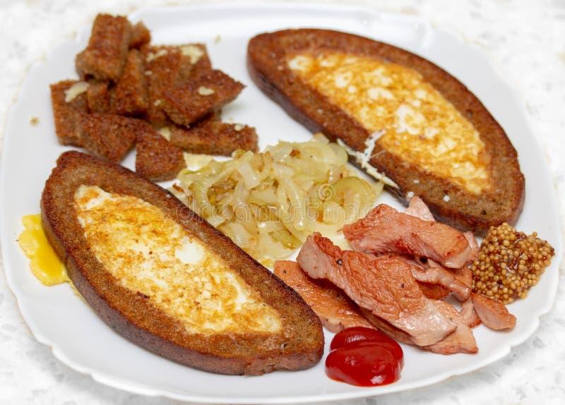 Dîner simple et chaleureux avec des oeufs au plat, des oignons et la saucisse d'un plat blanc photos stock