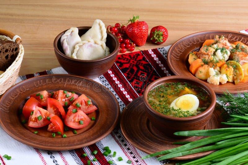 Dîner ukrainien national : potage aux légumes avec l'oeuf, salade, vareniki avec des baies, ragoût avec la nappe sur une table en photos stock