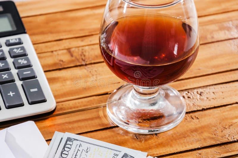 Dólar americano, calculadora, pena e um vidro do vinho em um fundo de madeira imagem de stock