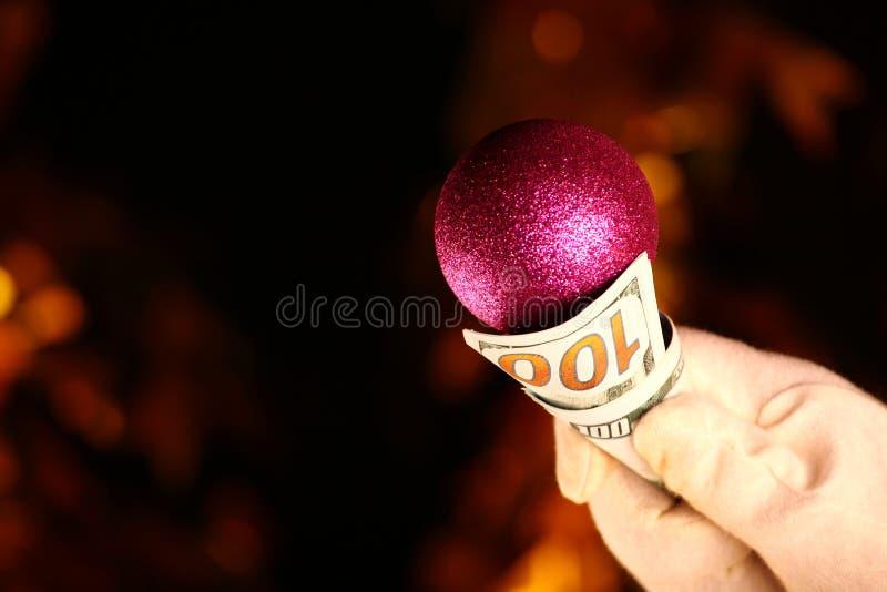 Dólar blanco del dinero de la bola de los juguetes del Año Nuevo de los guantes de la mano foto de archivo