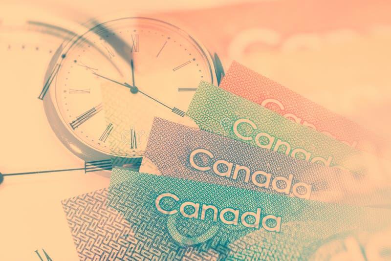 Dólar canadiense y reloj imagen de archivo libre de regalías