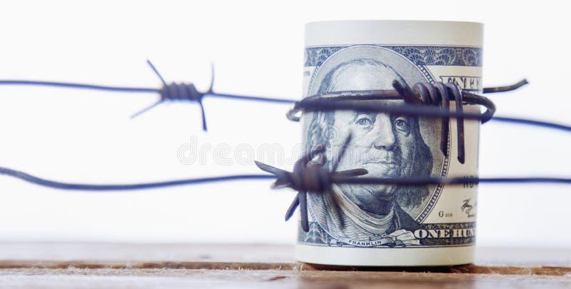 Dólar de EE. UU. envuelto en alambre de púas como símbolo de la guerra económica, foto de archivo libre de regalías